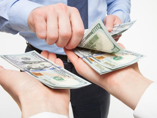 A businessman putting hundred dollar bills into outstretched hands.