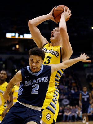 Marquette's Henry Ellenson shoots past Maine's Kevin Little (2) during the first half of an NCAA college basketball game Saturday in Milwaukee.