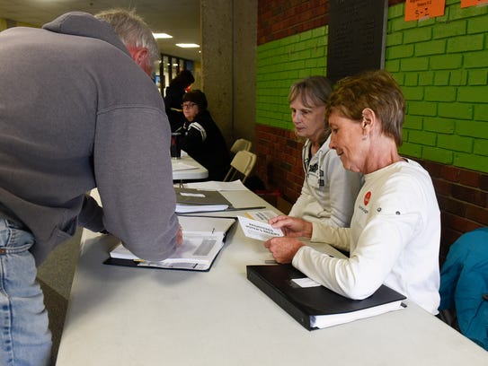 Voters sign in with the help of election judges at Pleasantview Elementary School on May 23, 2017 in Sauk Rapids.