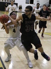 Alamogordo's Santiago Lechuga, left, tries to score in the paint while being guarded by Deming's Abel Chavez.
