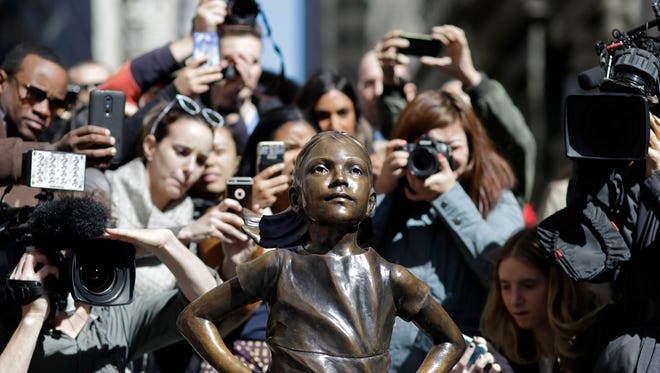 "People stop to photograph the Fearless Girl statue Wednesday in New York. The statue was created by Lewes artist Kristen Visbal and installed by investment firm State Street Global Advisors. An inscription at the base reads, ""Know the power of women in leadership. She makes a difference."""