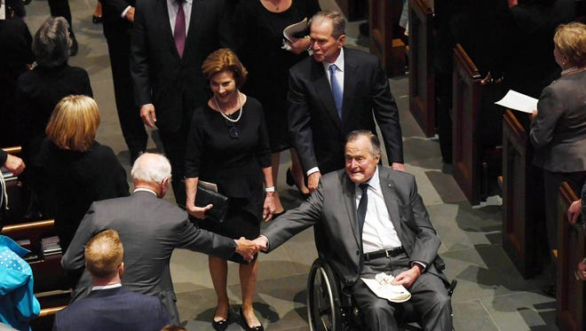 Former President George H.W. Bush, pushed by his son and former president George W. Bush, exits the funeral for his wife Barbara Bush at St. Martin's Episcopal Church in Houston.