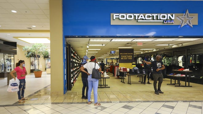 Shoppers wait in line, six feet apart, as FOOTACTION in the Westgate Mall in Brockton limits the number of customers in the store at a time on Wednesday, June 10, 2020.