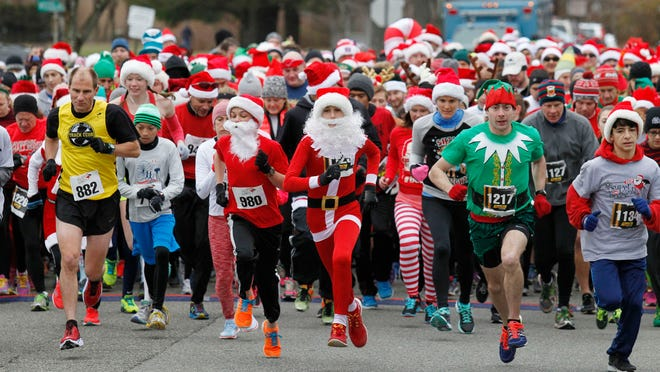 The Race gets underway during the second annual Super Santa 5K race held at at Ginty Field in Morris Twp. The first place winner, Mike Fonderr of Princeton, age 28, is seen in the front row, second from the right, wore an elf suit.
