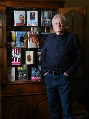 Nashville author Tom Carter stands in his Bellevue home office with some of autobiographies and other books that he has written of the years, including Reba and George Jones.