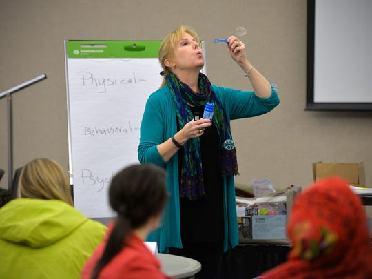 Ellen Ewald, mental health first aid instructor, blows