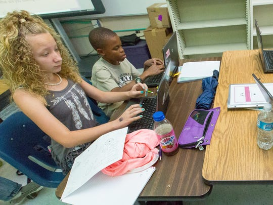 Kalynn Euller, 12, from left, Josiah Tomlin, 12, Becky Mehlert, 11, and Aubrianna Martinez, 12, work on laptops in class on Wednesday, May 18, 2016, at White SandsSchool.