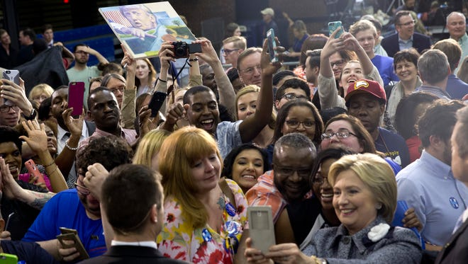 A person on the audience hold up an image of Republican presidential candidate Donald Trump as Democratic presidential candidate Hillary Clinton greets supporters and takes photos during a campaign event at the Grady Cole Center in Charlotte, N.C., Monday, March 14.