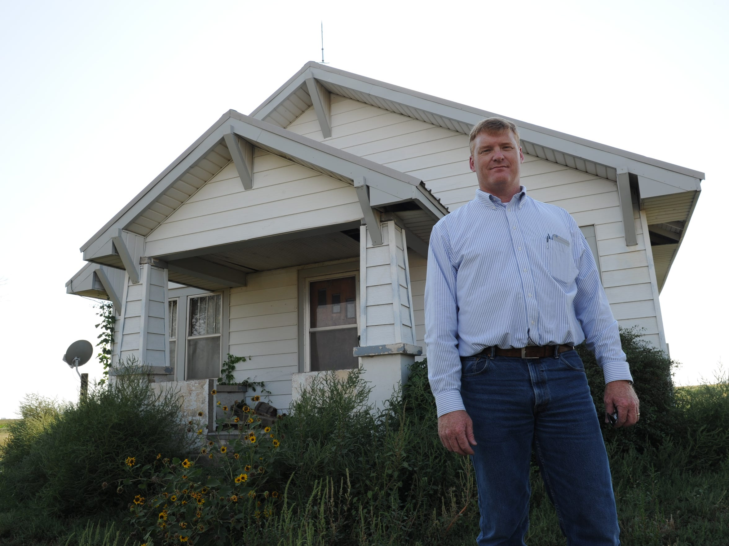 Jay Garetson stands in front of a farmhouse where he lived as a young boy. No one has been able to live in it since its well went dry two years ago. He said he fears more houses will be abandoned in the area in the coming years unless steps are taken to slow the decline of the Ogallala Aquifer.