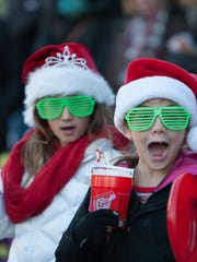 Henley Bednar (left) and Mia Hayden took in last year's parade during Christmas in the Village in Zionsville.