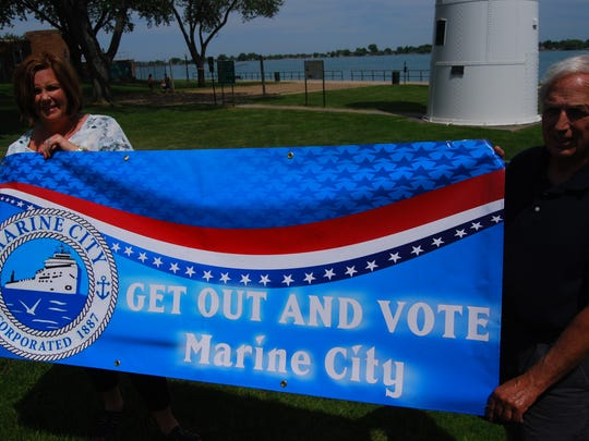 Marine City Clerk Krisetn Baxter and Gary Kohs hold a banner urging resident to register and to vote.