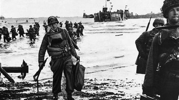 U.S. assault troops, laden with equipment, wade through the surf to a Normandy beach from landing craft in June 1944 to support those who had gone before in the D-Day assault.