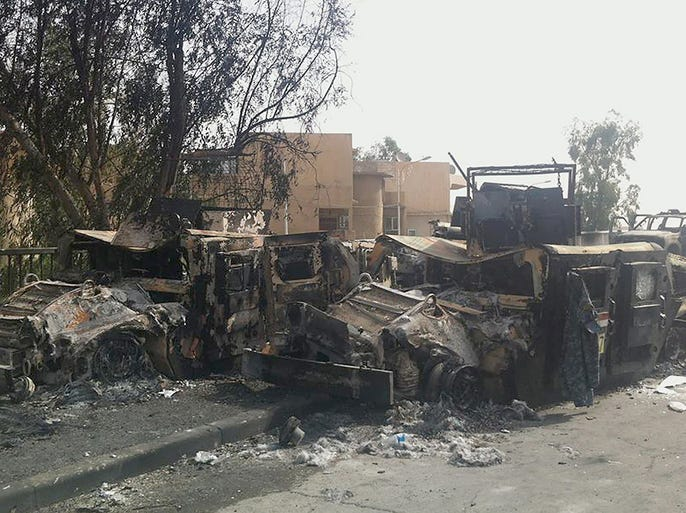Burned Iraqi army armored vehicles litter a street in Mosul. The militants have vowed to march on to Baghdad.