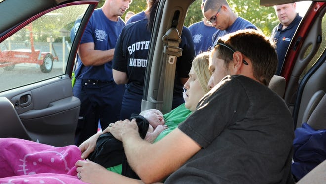 The 25-year-old woman who gave birth in car near Country Club Drive and Fifth Place holds her daughter following the birth Wednesday morning in Mesa.