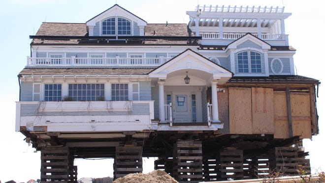 In this May 12, 2014, photo, a house on the Mantoloking, N.J., beachfront is being elevated to protect against future storms such as Superstorm Sandy.