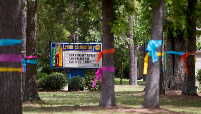 Ribbons are tied around trees in front of Lemm Elementary School in Spring, Texas, on Thursday.