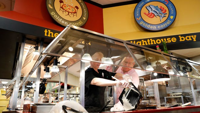 Tina Weber, left, and Jim Rimar, operations manager at the Lancaster Golden Corral restaurant, switch pans on the buffet line Thursday, July 12, 2018, in Lancaster. Golden Corral restaurants are offering free Hepatitis A vaccines to employees in eight location in Ohio, West Virginia and Kentucky in an effort to curb an outbreak in this part of the country.