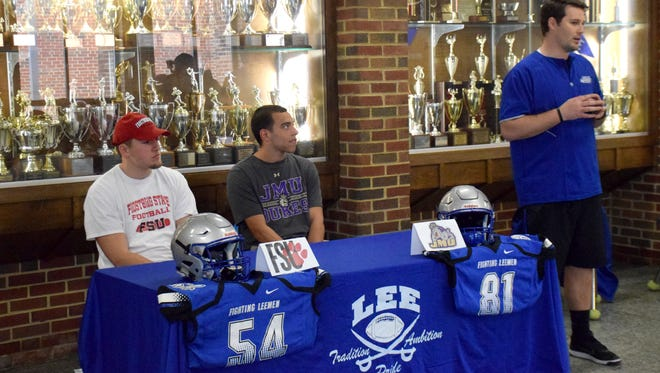 Robert E. Lee head football coach Scott Girolmo addresses the media and attendees as seniors Dylan Culpen, left, and Tre Simmons prepare to announce their collegiate choices on Wednesday, April 25, 2018, at Robert E. Lee High School in Staunton, Va., Culpen will play football for Frostburg State University in Maryland, while Simmons will walk on at James Madison.