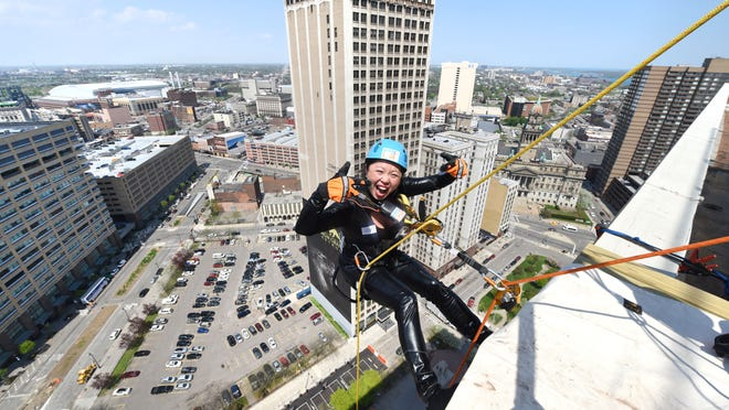 """Sherry Wong of Grosse Pointe Woods, dressed as Cat Woman, rappels off the First National Building on Friday as part of the """"Over the Edge"""" project to raise money for earthquake victims in Nepal."""