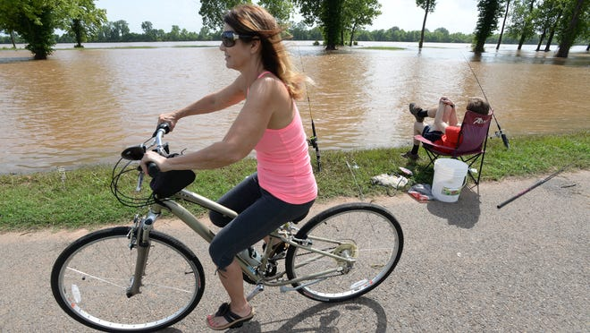 Debbie Prestridge-Davis speeds past Jacob Hannigan on her bicycle while riding on the Arthur Ray Teague Parkway running trail. The Red River has risen to the point that anglers can now fish from the edge of the running trail.