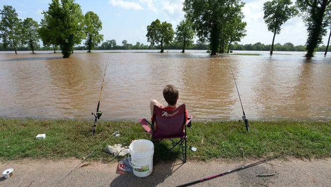 Jacob Hannigan relaxes as he fishes from the edge of the Arthur Ray Teague Parkway running trail now that waters from the Red River have flooded into the area.