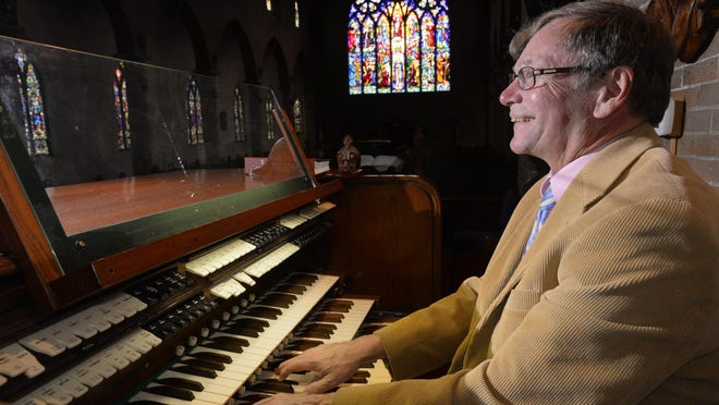 Outgoing St. Paul's choir master and organist Steve Lange smiles as he plays the pipe organ in the church. Lange is retiring after 45 years as a staple of St. Paul's Episcopal Church in downtown Lansing.