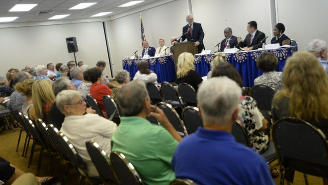 Moderator John Lorick stood in-between the six candidates who are running for Caddo DA during the public forum Monday evening at the Southern Hills Homeowner's Association.
