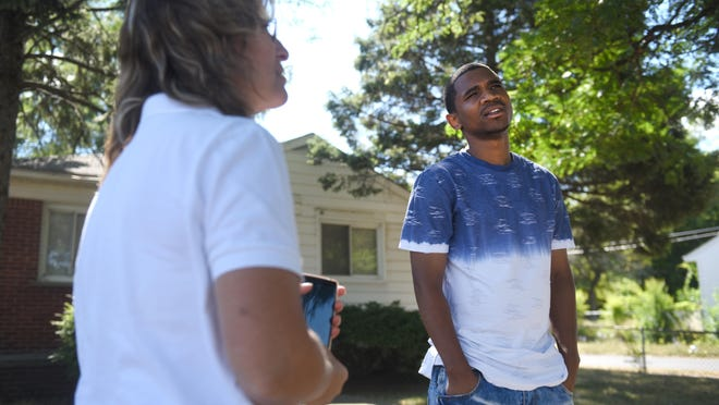 Davontae Sanford, right, listens to family attorney Valerie Newman outside his childhood home in Detroit. An eight-year struggle to exonerate him of murder was stymied until he finally was freed.