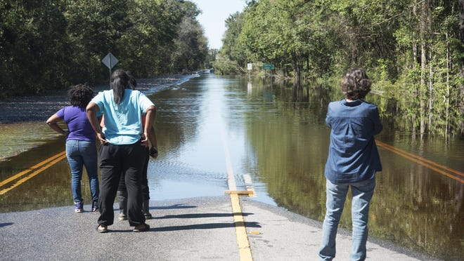 Floodwaters caused by rain from Hurricane Matthew block NC Highway 41 west at the Bladen and Robeson County line outside of Lumberton, N.C., Monday, Oct. 10, 2016. (AP Photo/Mike Spencer)
