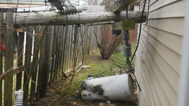A power transformer rests in a backyard on Thursday March 9, 2017 of a home located at Archer Street in Detroit as a tree branch snapped power pole after high winds caused massive power outages.