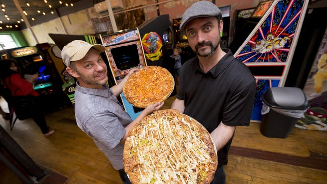 (From left) Co-owners Timothy Tharp, holding a Super Saiyan pizza, and David Gregory, holding a Naplam Breath pizza. The Super Saiyan has red sauce, blue cheese, cheddar, parmesan, and Cheetos. The Napalm Breath pizza is a white pie with fresh garlic, Cheez, blend, feta, yellow peppers, white onion, garlic aioli and fried garlic. Photos are of the Pop + Offworld pizza and arcade bar, in Detroit, September 5, 2017. (David Guralnick / The Detroit News)