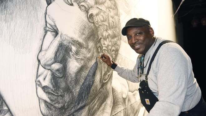 """Artist Hubert Massey works on """"Detroit: Crossroad of Innovation,"""" a 30- foot-by-30-foot charcoal drawing that features many symbolic images. The fresco will eventually be painted on Cobo Center's second floor."""