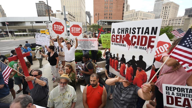 People carry signs protesting the deportation of Iraqi-American immigrants as members of the Chaldean community rallied at the McNamara Federal building in Detroit in June 2017.