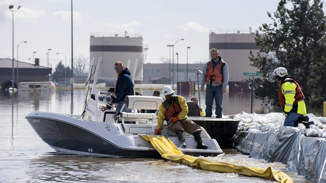 In this March 18, 2019 photo, environmental restoration employees deploy a containment boom from a boat on Offutt Air Force Base in Neb., as a precautionary measure for possible fuel leaks in the flooded area.