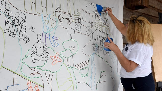 Boone County Recorder of Deeds Nora Dietzel paints a portion of the Boone County Bicentennial Mural during the 2019 Heritage and Crafts Festival at Nifong Park. The 2020 festival, scheduled for September, has been canceled because of concerns abotu the coronavirus that causes COVID-19.