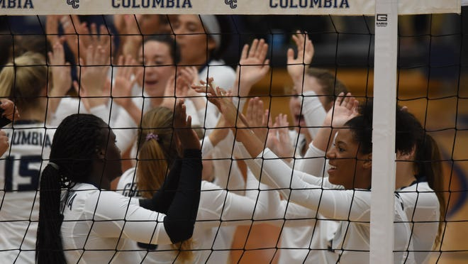 Columbia College volleyball players high-five before a 2018 home match.