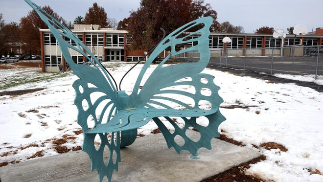 A metal butterfly bench dedicated to the late Mayor Darwin Hindman sits next to the Russell Boulevard Elementary School playground.