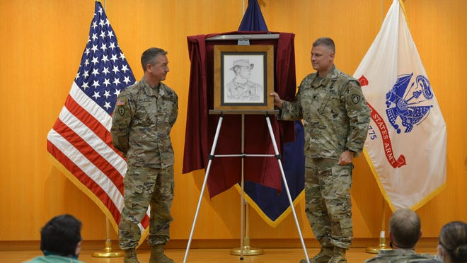 Staff Sgt. Daniel Trojecki and Lt. Col. Shanon Cotta unveil the portrait of Staff Sgt. Harold Gray.