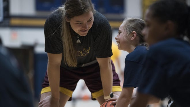 Former Freeport Aquin and Arizona State basketball star Sophie Brunner talks to fifth-grader Hailey Pizzolato, 10, during dribbling practice at the Aquin High School basketball camp on June 12, 2019, in Freeport. Brunner recently accepted a job as an assistant basketball coach at Rockford Christian.