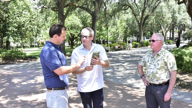 From left, Anthony Wallace discusses reading the map with Kevin Lewis and Dr. Bob Johnson at Forsyth Park in Savannah.