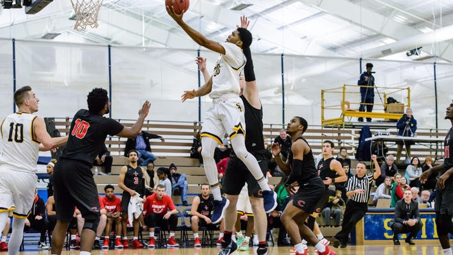 Siena Heights' Keith Jordan Jr. (30) shoots past Concordia (Ann Arbor)'s Paul Zisk during a Wolverine-Hoosier Athletic Conference game on Nov. 28, 2018. Jordan is the latest Saint to find a chance to play professionally overseas, as he signed a contract to play for Templeogue Basketball Club in Dublin.