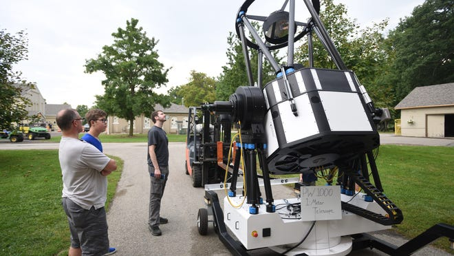 Wayne Schroeder, his son Cody, and Joshua Hanauer, all of Columbia City, Ind., view a PlaneWave Instruments 1-meter telescope during an open house Sept. 21 at the telescope manufacturer's Adrian campus. PlaneWave has scheduled an open house for Tuesday, Oct. 20.