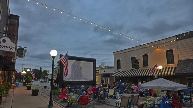 """People watch """"A Dog's Way Home"""" June 20, 2019, in downtown Blissfield. While the """"Movies on Lane"""" program will resume this month, the first installment won't be on Lane Street. Instead, it will be Thursday, June 18, in the parking lot of either Blissfield High School or the American Farm Museum and Education Center in a drive-in format."""