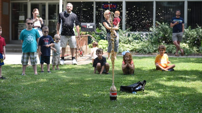 "Adrian College professor Sarah Hanson uses Mentos candy and Diet Coke to demonstrate the force of a volcano during a presentation on volcanoes, titled ""Lava Learning"" July 23, 2019, at the Schultz-Holmes Memorial Library in Blissfield."