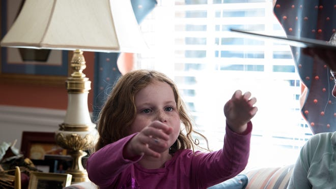 """Grace reaches out for her new favorite toy, an iPad given to her by a friend. Scott describes it as """"her strength"""""""