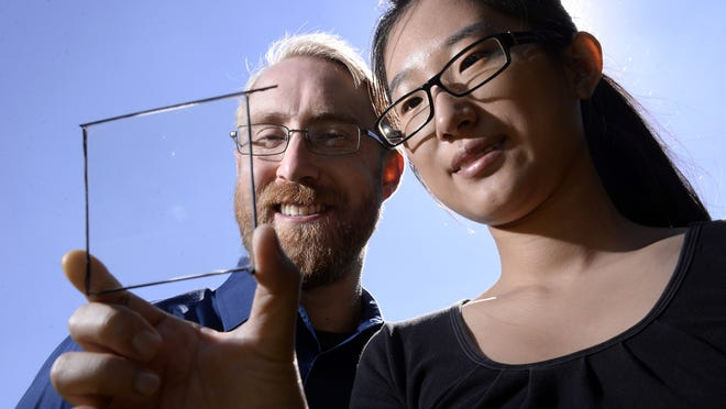 Richard Lunt and MSU graduate student Yimu Zhao show a transparent luminescent solar concentrator module.