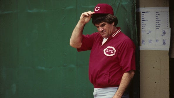 Manager Pete Rose of the Cincinnati Reds watches from near the dugout as his team plays the Pittsburgh Pirates at Three Rivers Stadium in 1987 in Pittsburgh, Pennsylvania.