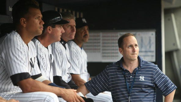 Alex Rodriguez of the New York Yankees sits on the bench, joined by Yankees General Manager Brian Cashman before a game against the Seattle Mariners at Yankee Stadium on July 2, 2009 in the Bronx borough of New York City.