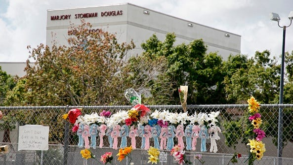 Memorials are seen on a fence surrounding Marjory Stoneman Douglas High School in Parkland, Florida on Feb. 21, 2018.
