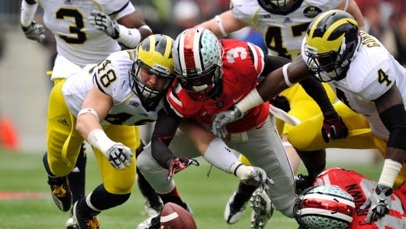 COLUMBUS, OH - NOVEMBER 24: Desmond Morgan #48 of the Michigan Wolverines and Corey Brown #3 of the Ohio State Buckeyes dive for a loose ball after Corey Brown #10 of the Ohio State Buckeyes fumbled a punt return at Ohio Stadium on November 24, 2012 in Columbus, Ohio. Michigan recovered the ball and scored a touchdown. (Photo by Jamie Sabau/Getty Images)